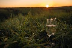 Ρομαντικό γυαλί της συνεδρίασης κρασιού στην παραλία στα ζωηρόχρωμα ποτήρια ηλιοβασιλέματος του άσπρου κρασιού ενάντια στο ηλιοβα στοκ εικόνες