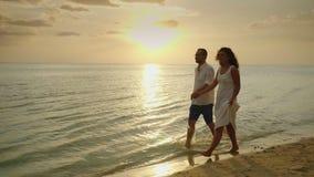 Ρομαντικό ερωτευμένο περπάτημα ζευγών θαλασσίως στο ηλιοβασίλεμα Μήνας του μέλιτος και διακοπές από την έννοια θάλασσας απόθεμα βίντεο