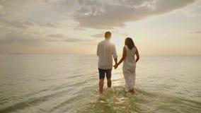 Ρομαντικό ερωτευμένο περπάτημα ζευγών θαλασσίως στο ηλιοβασίλεμα Μήνας του μέλιτος και διακοπές από την έννοια θάλασσας φιλμ μικρού μήκους