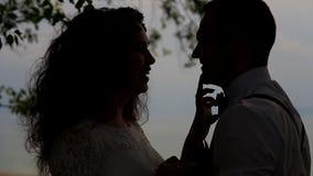 Ρομαντικό ζεύγος ενάντια στον ουρανό στο backlight Η νέα γυναίκα αγγίζει ήπια ένα δάχτυλο στη μύτη του αγαπημένου απόθεμα βίντεο