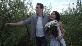 Ρομαντικό ζεύγος ερωτευμένο παίρνοντας έναν περίπατο στον οπωρώνα απόθεμα βίντεο