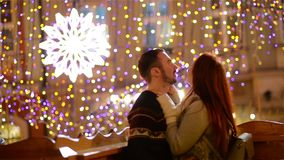 Ρομαντικό ζεύγος με την καυκάσια εμφάνιση που φιλά και που αγκαλιάζει Τα φω'τα και τα πυροτεχνήματα είναι στο υπόβαθρο νεολαίες ζ απόθεμα βίντεο