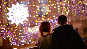 Ρομαντικό ζεύγος με την καυκάσια εμφάνιση που φιλά και που αγκαλιάζει Τα φω'τα και τα πυροτεχνήματα είναι στο υπόβαθρο νεολαίες ζ φιλμ μικρού μήκους