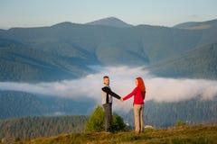 Ρομαντικό ζεύγος που απολαμβάνει μια ελαφριά ομίχλη πρωινού πέρα από τα βουνά Στοκ Εικόνες