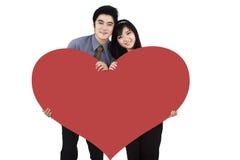 Ρομαντικό ζεύγος που κρατά μια μεγάλη κόκκινη καρδιά Στοκ φωτογραφία με δικαίωμα ελεύθερης χρήσης