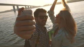 Ρομαντικό ζεύγος που παίρνει τη φωτογραφία τους κοντά στη γέφυρα κάτω από τις ακτίνες ήλιων απόθεμα βίντεο