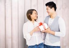 Ρομαντικό ζεύγος που φαίνεται πρόσωπο με πρόσωπο και που κρατά το κιβώτιο δώρων Στοκ Εικόνες