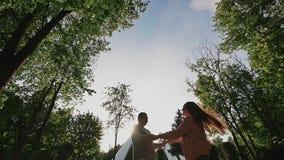 Ρομαντικό ζεύγος σε ένα πράσινο θερινό πάρκο Κρατούν τα χέρια, συστροφή μεταξύ τους στις ακτίνες του φωτός του ήλιου ευτυχής από  απόθεμα βίντεο