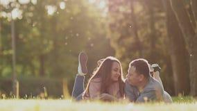 Ρομαντικό ζεύγος σε ένα πράσινο ξέφωτο το καλοκαίρι Βρίσκονται στα στομάχια τους, πόδια επάνω Εξετάζουν ο ένας τον άλλον με την τ απόθεμα βίντεο