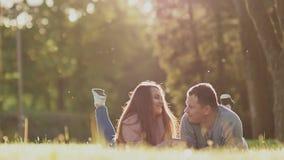 Ρομαντικό ζεύγος σε ένα πράσινο ξέφωτο το καλοκαίρι Βρίσκονται στο στομάχι, πόδια επάνω Εξετάζουν ο ένας τον άλλον συγκινητικά αυ απόθεμα βίντεο