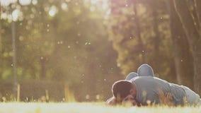 Ρομαντικό ζεύγος σε ένα πράσινο ξέφωτο το καλοκαίρι Παίζουν ο ένας με τον άλλον, που βρίσκεται στη χλόη Ευτυχής μαζί στις ακτίνες απόθεμα βίντεο