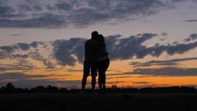 Ρομαντικό ζεύγος σκιαγραφιών, που εξετάζεται το ερυθρό ηλιοβασίλεμα, που αγκαλιάζει το ένα το άλλο φιλμ μικρού μήκους