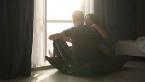 Ρομαντικό ζεύγος στις πυτζάμες που κάθεται στο πάτωμα το πρωί Όμορφη νέα ενήλικη καυκάσια συνεδρίαση γυναικών και ανδρών μέσα απόθεμα βίντεο