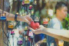 Ρομαντικό ζεύγος την ημέρα βαλεντίνων Η ευτυχής χαρούμενη γυναίκα που δίνει την καρδιά ανδρών διαμορφώνει λίγο μαξιλάρι σε ένα φω στοκ φωτογραφία