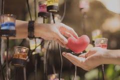 Ρομαντικό ζεύγος την ημέρα βαλεντίνων Η ευτυχής χαρούμενη γυναίκα που δίνει την καρδιά ανδρών διαμορφώνει λίγο μαξιλάρι σε ένα φω στοκ φωτογραφίες