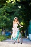 Ρομαντικό κορίτσι στις ακτίνες των γύρων φωτός του ήλιου στο αναδρομικό ποδήλατο στοκ εικόνες με δικαίωμα ελεύθερης χρήσης