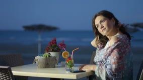 Ρομαντικό νέο κοκτέιλ κατανάλωσης γυναικών, ονειροπόλος κυρία που φαίνεται τη νύχτα seascape φιλμ μικρού μήκους
