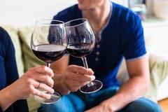 Ρομαντικό νέο ψήσιμο ζευγών με το κόκκινο κρασί καθμένος στο θόριο Στοκ Εικόνες