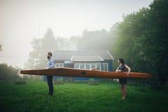 Ρομαντικό ξύλινο κανό ερωτευμένης εκμετάλλευσης ζευγών Στοκ φωτογραφία με δικαίωμα ελεύθερης χρήσης