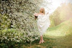 Ρομαντικό πλήρες πορτρέτο OD ύψους μια ξανθή γυναίκα στο άσπρο φόρεμα με μια ανθοδέσμη που στέκεται tiptoe κοντά στο ανθίζοντας δ στοκ εικόνες