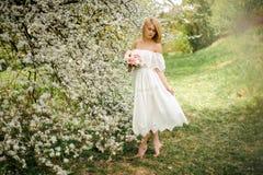 Ρομαντικό πλήρες πορτρέτο OD ύψους μια ξανθή γυναίκα στο άσπρο φόρεμα με μια ανθοδέσμη που στέκεται κοντά στο ανθίζοντας δέντρο στοκ εικόνες