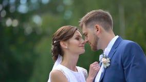 Ρομαντικό πορτρέτο κινηματογραφήσεων σε πρώτο πλάνο Η θαυμάσια νύφη με το φανταστικό χαμόγελο τρίβει tenderly και φιλά τη μύτη τη απόθεμα βίντεο