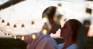 Ρομαντικό πορτρέτο του ευτυχούς ζεύγους beautfiul που χαμογελά και που τρίβει τις μύτες κοντά στη σειρά των λαμπτήρων 4k μήκος σε φιλμ μικρού μήκους
