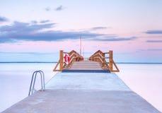 Ρομαντικό πρωί στο λιμάνι Αποβάθρα τουριστών επάνω από το σιωπηλό μπλε νερό Ηλιόλουστος ρόδινος μπλε ουρανός Στοκ Φωτογραφία