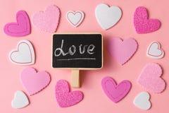 Ρομαντικό υπόβαθρο ημέρας βαλεντίνων Ένας μεγάλος αριθμός καρδιών του διαφορετικού μεγέθους με την αγάπη λέξης Στοκ Φωτογραφίες