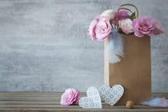 Ρομαντικό υπόβαθρο με τα τριαντάφυλλα και τις χειροποίητες καρδιές στοκ εικόνα