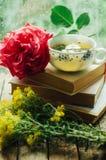 Ρομαντικό υπόβαθρο με το φλυτζάνι του τσαγιού, των λουλουδιών και του ανοικτού βιβλίου Στοκ εικόνα με δικαίωμα ελεύθερης χρήσης