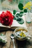 Ρομαντικό υπόβαθρο με το φλυτζάνι του τσαγιού, των λουλουδιών και του ανοικτού βιβλίου Στοκ Φωτογραφίες