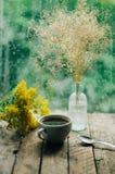 Ρομαντικό υπόβαθρο με το φλυτζάνι του τσαγιού, των λουλουδιών και του ανοικτού βιβλίου Στοκ φωτογραφία με δικαίωμα ελεύθερης χρήσης