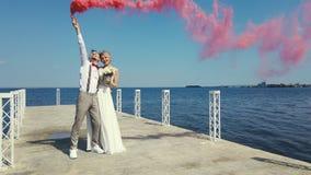 Ρομαντικό φιλί των newlyweds με το χρωματισμένο καπνό, βόμβες καπνού στα χέρια Είναι αγκάλιασμα, στεμένος στο α φιλμ μικρού μήκους