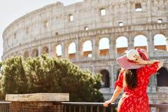 Ρομαντικό brunette που φορά την κόκκινη στάση φορεμάτων και καπέλων στοκ φωτογραφίες