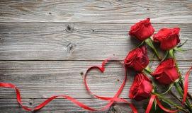 Ρομαντικό floral πλαίσιο με τα κόκκινα τριαντάφυλλα και κορδέλλα στο ξύλινο backgr Στοκ φωτογραφίες με δικαίωμα ελεύθερης χρήσης
