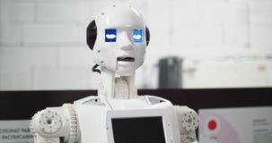 Ρομποτικές σύγχρονες τεχνολογίες Το ρομπότ εξετάζει τη κάμερα στο πρόσωπο Το ρομπότ παρουσιάζει συγκινήσεις 4K απόθεμα βίντεο
