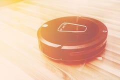 Ρομποτική ηλεκτρική σκούπα στο ξύλινο πάτωμα παρκέ, έξυπνος κενός, νέο στοκ εικόνα