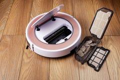 Ρομποτική ηλεκτρική σκούπα στο ξύλινο πάτωμα, που καθαρίζει το εμπορευματοκιβώτιο ρύπου Στοκ εικόνες με δικαίωμα ελεύθερης χρήσης