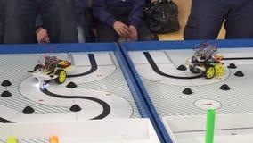 Ρομπότ στις ρόδες που κατασκευάζονται από τους προγραμματιστές στους ανταγωνισμούς μιας ρομποτικής Εκπαίδευση των παιδιών απόθεμα βίντεο