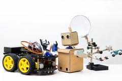 Ρομπότ στις ρόδες και ρομπότ με τη στάση χεριών στο άσπρο υπόβαθρο Στοκ Φωτογραφίες