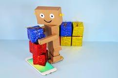 Ρομπότ φιαγμένο από χαρτόνι, δώρα και κινητό τηλέφωνο Στοκ εικόνες με δικαίωμα ελεύθερης χρήσης