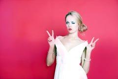 Δροσερή γυναίκα που φορά το άσπρο φόρεμα στο κόκκινο υπόβαθρο Στοκ Εικόνες
