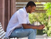 Δροσερός μαύρος τύπος που εξετάζει το τηλέφωνο κυττάρων Στοκ εικόνα με δικαίωμα ελεύθερης χρήσης