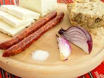 Ρουμανικό παραδοσιακό πρόχειρο φαγητό των λουκάνικων και του ψωμιού κρεμμυδιών τυριών σε ένα ξύλινο πιάτο Στοκ φωτογραφία με δικαίωμα ελεύθερης χρήσης