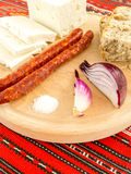 Ρουμανικό παραδοσιακό πρόχειρο φαγητό των λουκάνικων και του ψωμιού κρεμμυδιών τυριών σε ένα ξύλινο πιάτο Στοκ Φωτογραφίες