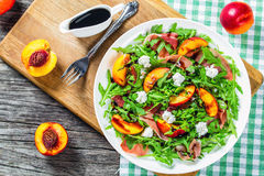 Ροδάκινα, σαλάτα τυριών arugula, prosciutto και αιγών με βαλσαμικό Στοκ Φωτογραφία