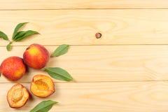 ροδάκινο Φρούτα με το πράσινο φύλλο στον ξύλινο πίνακα Τοπ άποψη με το διάστημα αντιγράφων στοκ εικόνες