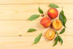 ροδάκινο Φρούτα με το πράσινο φύλλο στον ξύλινο πίνακα Τοπ άποψη με το διάστημα αντιγράφων στοκ φωτογραφία