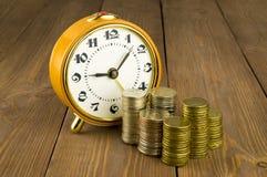 Ρολόγια και νομίσματα σε έναν ξύλινο πίνακα Στοκ Εικόνα